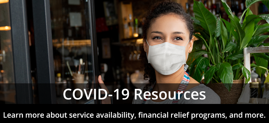woman with mask in front of a build - message saying COVID-19 Resources