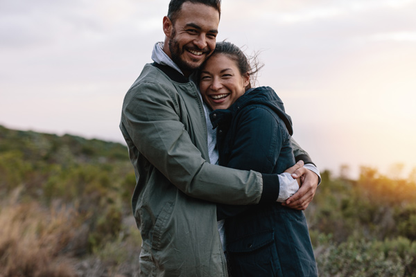 couple outdoors holding each other smiling